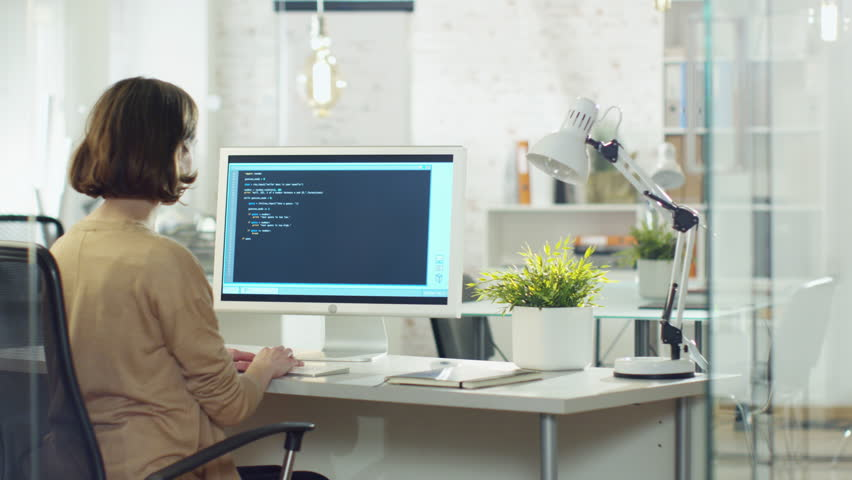 Young Creative Woman Developer Writes Code on Her Desktop Computer. She Sits in Her Modern developer Office. Shot on RED Cinema Camera in 4K (UHD). | Shutterstock HD Video #22195276