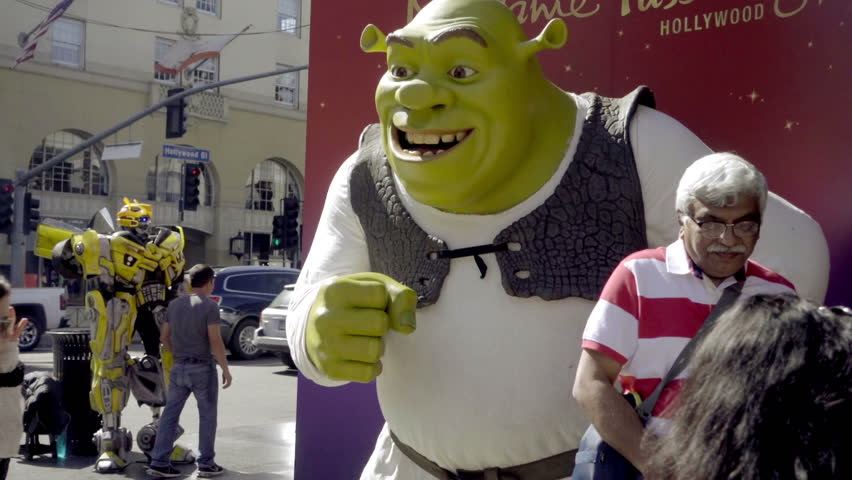 LOS ANGELES - OCT 23, 2016: Tourists Posing In Front Of Shrek Statue On Hollywood Boulevard In LA California. HW Blvd is a major thoroughfare and tourist attraction in Los Angeles.
