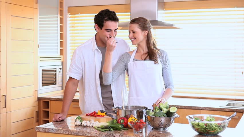 Husband tasting his wife's cooking with a spoon in a kitchen