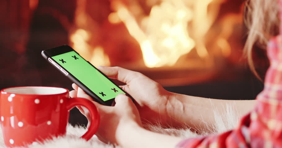 Cinemagraph - Unrecognizable Woman Hands Using SmartPhone by the Burning Fireplace - Close Up. 120FPS. Female hands with phone green screen and cup by cozy fireside. Searching internet, using app.