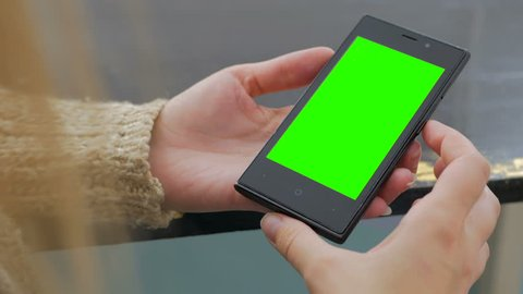 Woman looking at vertical smartphone with green screen. Close up shot of woman's hands with mobile