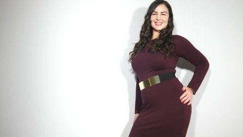 Happy plus size model woman dancing in studio