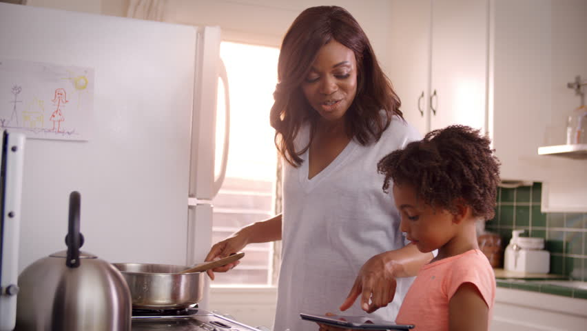 Mother And Daughter At Home Preparing Meal In Kitchen