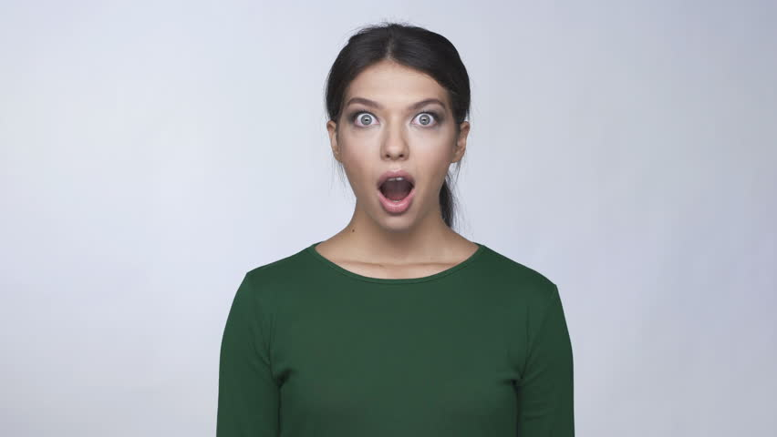 Shocked astonished pretty young woman in green sweater touching her face
