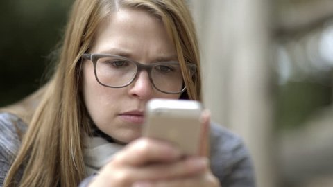Young Female looking perplexed at her cell phone 4k