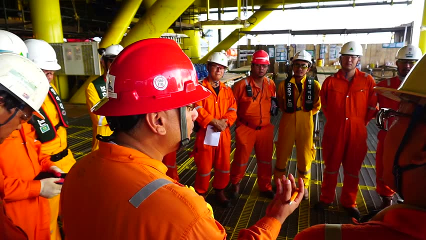 KELANTAN, MALAYSIA - JAN 05 2016 : Unidentified Korean and local offshore workers complete with Personal Protective Equipment (PPE) standing together to listen safety briefing prior to start work.