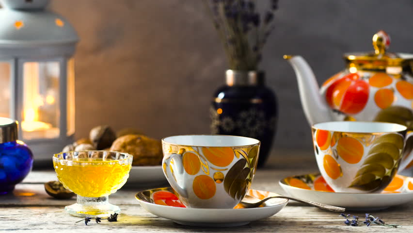 tea time, tea is pouring from the teapot in old fashioned cups of orange and gold colors on wooden desk with candle and honey