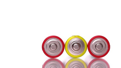 Three AAA batteries rolling on white background