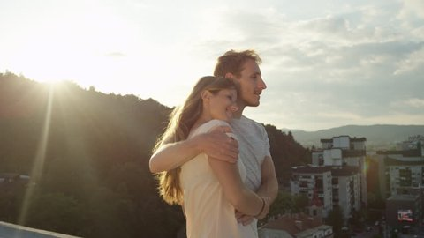 SLOW MOTION, CLOSE UP: Caring boy taking his girl on romantic date embracing and caressing her on the edge of skyscraper rooftop above beautiful city surrounded by overgrown hills at stunning sunrise