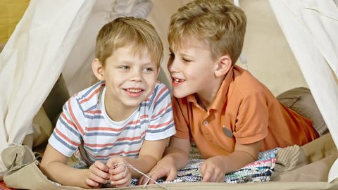 Little boy lying in teepee with laughing friend and telling him jokes