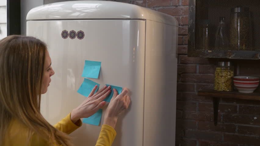Young busy woman make note glues sticky on refrigerator. Business woman working at home. Caucasian adult lady at home kitchen. Call me. | Shutterstock HD Video #22414006