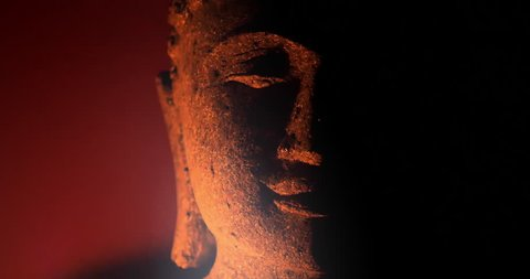 Calm and peaceful face of Buddha statue illuminated by candle light in darkness