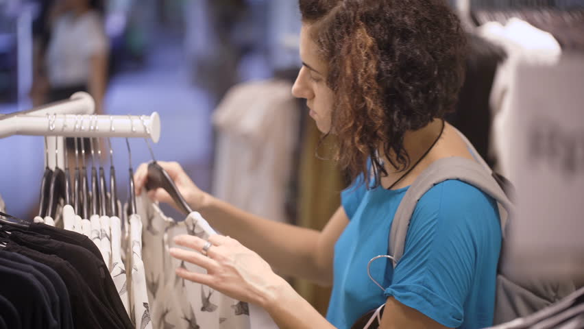 Fashionista chooses a new outfit in the store. Curly brunette touches dresses that hang on a hanger in the store. Pretty girl dressed in a blue T-shirt with a backpack on his shoulders.