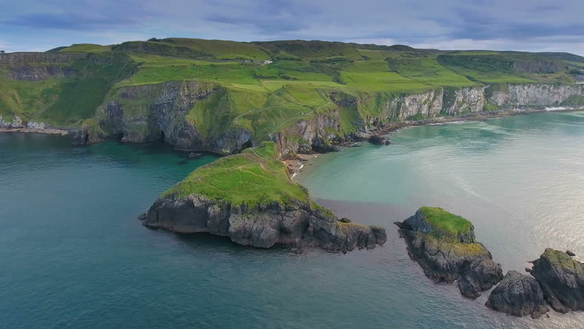 Landscape view of the Carrick-a-Rede Rope Bridge with the big ocean fronting the mountain cliff in Ireland in Ireland