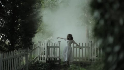 VIRGINIA - SUMMER 2016 - Reenactment, Recreation -- Ghostly, undead woman in smoky garden / graveyard.  Paranormal, poltergeist.  Mystery woman with pale pallor, 19th century clothing in misty smoke