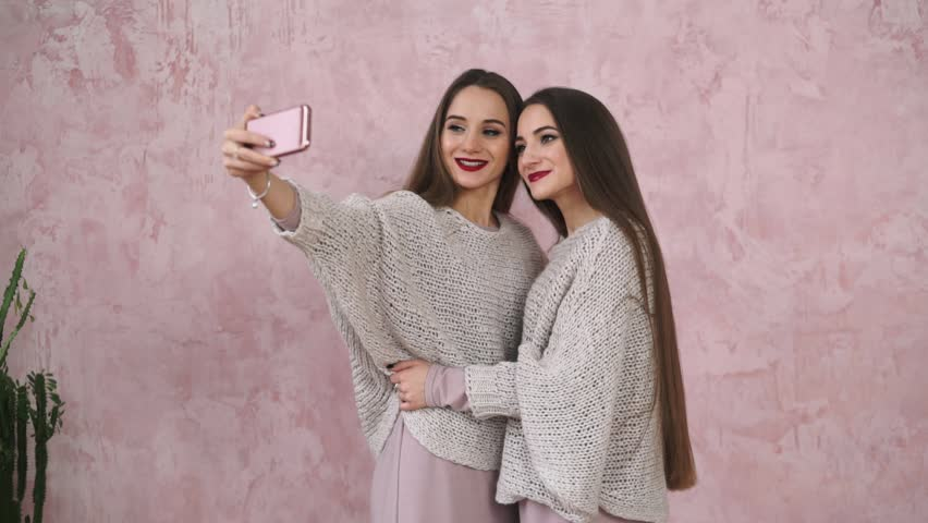 Friendship and technology. Slow motion. Two pretty caucasian long-haired twins sisters in cozy sweaters taking selfie with smart phone on pink background. | Shutterstock HD Video #22469542