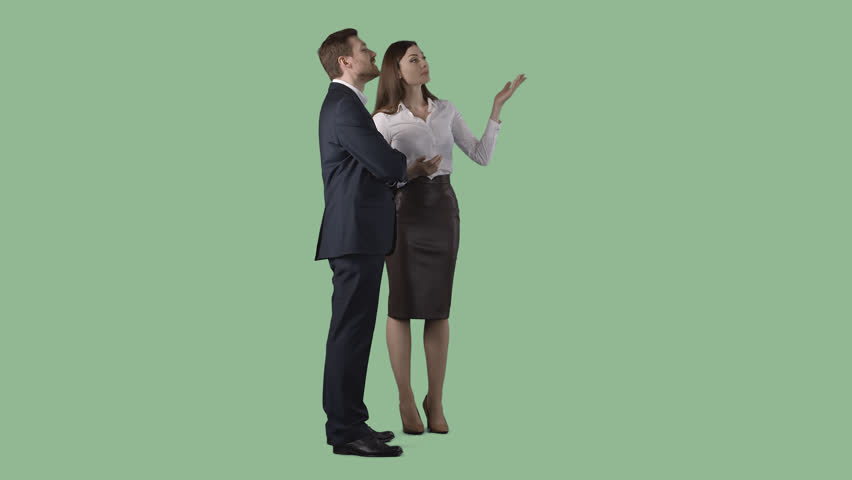 Pretty woman in office clothes is standing with respectable business man and showing something to him. Green screen clip with alpha channel