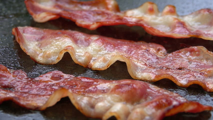 Close-up of a slice of bacon fried on a hot grill