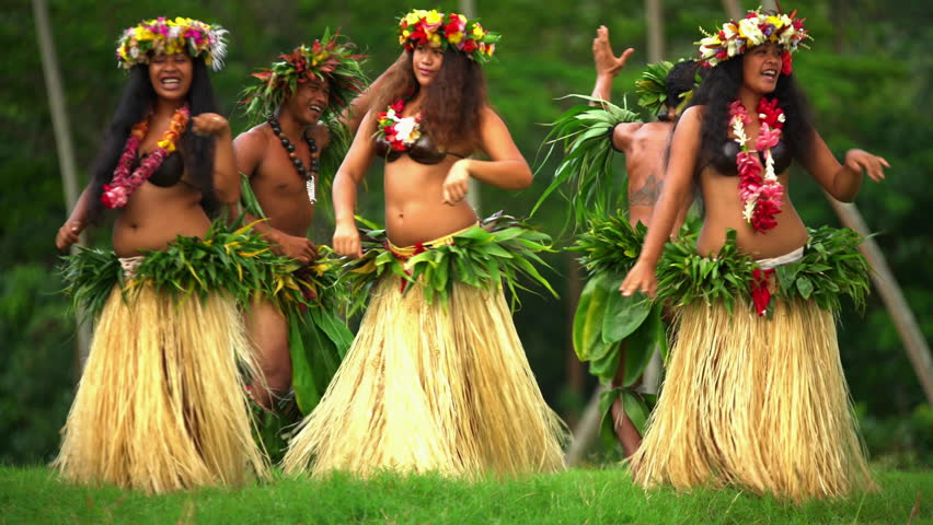 Barefoot Tahitian males in warrior dress with females in hula skirts and flower headdress performing a traditional dance at celebration ceremony French Polynesia