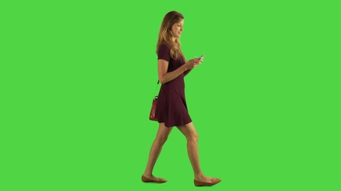 Young woman walking sideways and chating in an app, full body shot over a green screen.