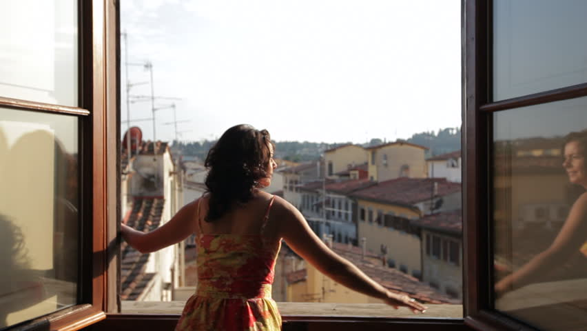 MH DS Woman Opening Windows Overlooking Old Town Rooftops / Florence, Italy