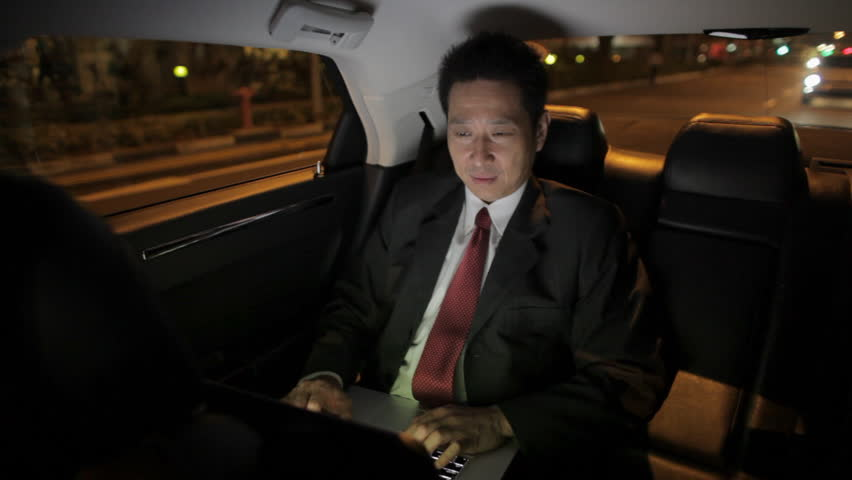 MH Businessman Riding in Back Seat of Car Working on Laptop at Night / Singapore