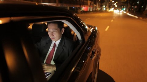 MH TS POV Businessman Riding in Back Seat of Car Working on Laptop at Night / Singapore