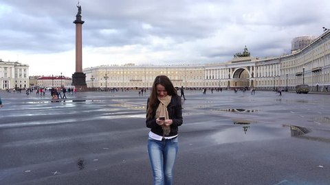 Young brunette woman stroll over Palace Square, stares at smart phone. Tourist girl comes to central Saint Petersburg area after rain, sights in background, Alexander Column, General Staff Building