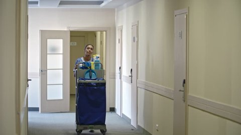 Female Latin American housekeeper in uniform pushing trolley with cleaning products and walking along hotel corridor