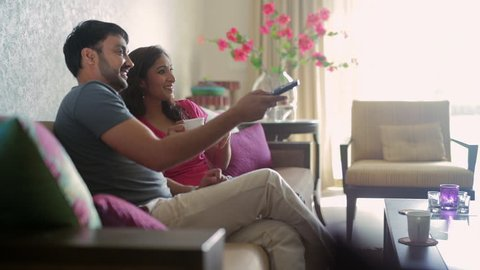 MS Mid-adult couple watching TV in living room / India