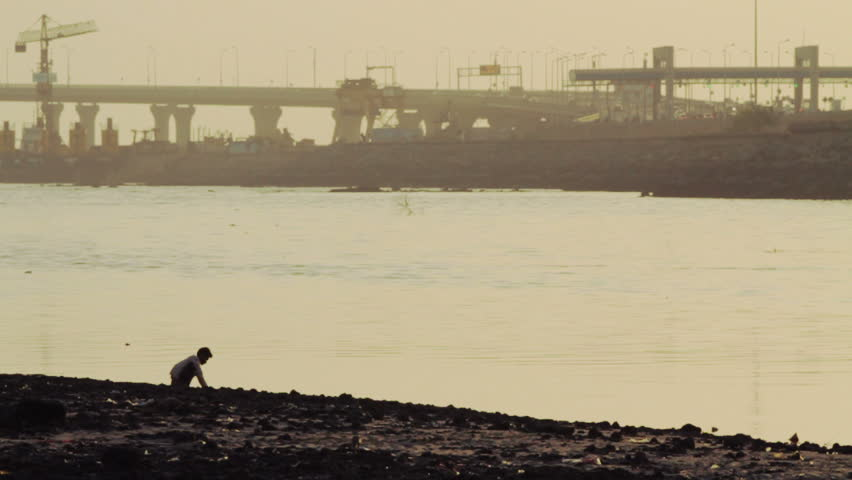 The silhouette of a child sitting on the river shore in Mumbai, drawing in the sand.