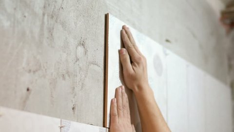 Unrecognizable ceramist is laying tiles on bathroom wall. Slow motion