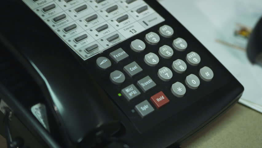person's hands placing a telephone call on an office phone