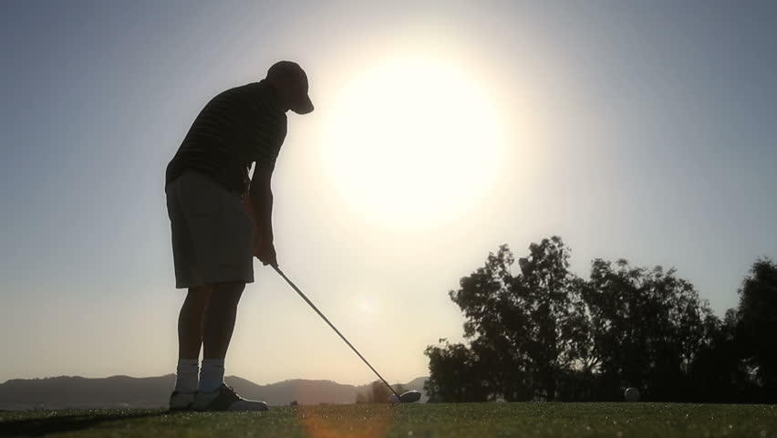 Silhouette of golfer driving the ball