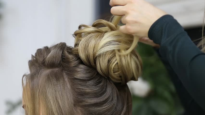 Hairdresser creating complicated evening and wedding hairstyles at barbershop salon. Close-up of hands corrects hair curls and strands