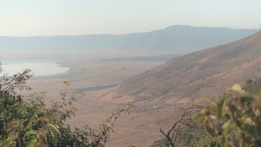 AERIAL: Breathtaking view of Ngorongoro conservation area from the rim of volcanic caldera with charming salt lake Magadi in the middle. Stunning montane forest growing on steep wall of volcano crater