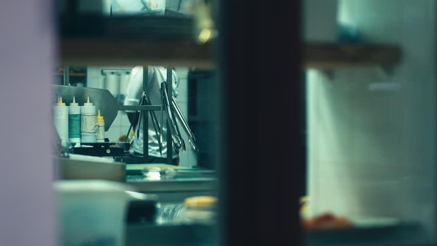 Restaurant Kitchen Video hd cinemagraph. handsome caucasian chef standing in the restaurant