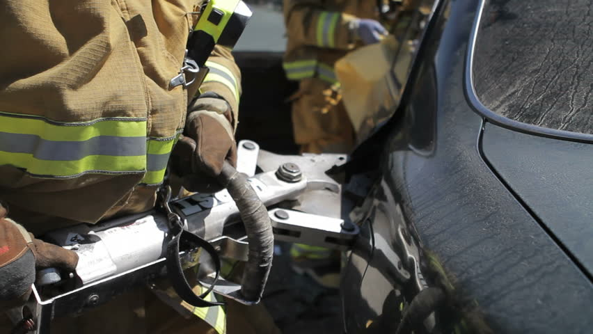 Fireman using the jaws of life at crash site