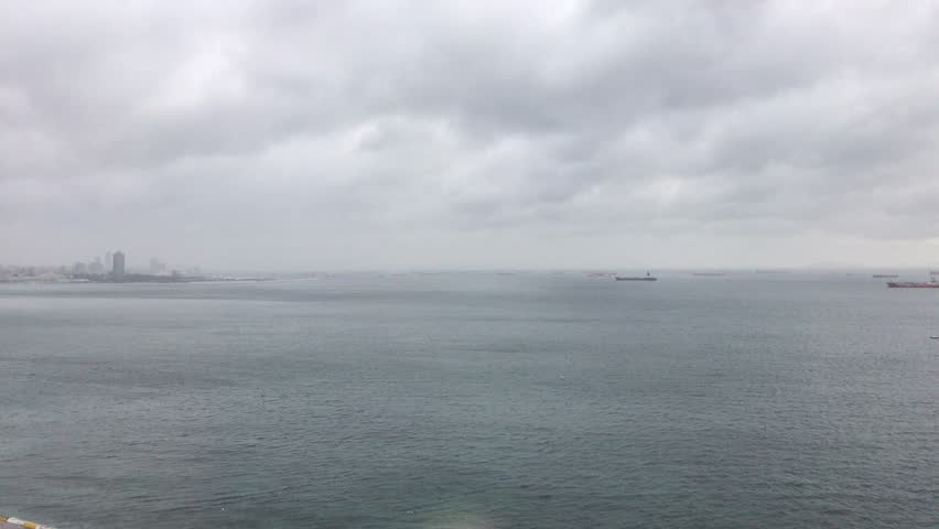 Ships anchored close to the coast on an overcast cloudy day #22720177