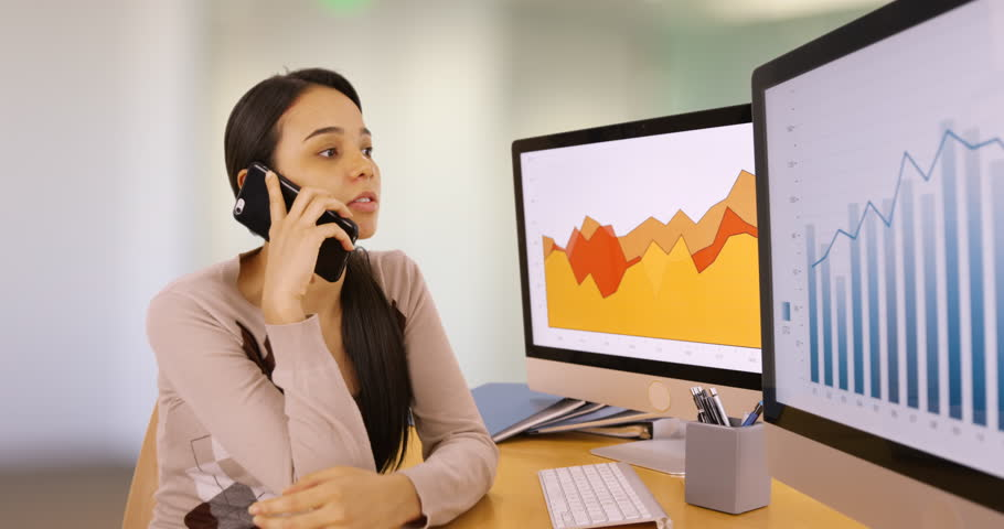 A young businesswoman talks on her mobile phone referencing the graphs. A young woman talks on her smart phone about business. 4k
