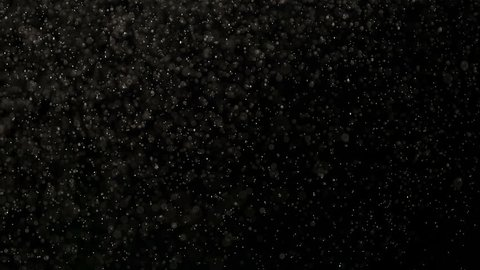 White Microparticles in Flight. Small white particles flow in the air on a black background. Slow Motion at a rate of 240 fps