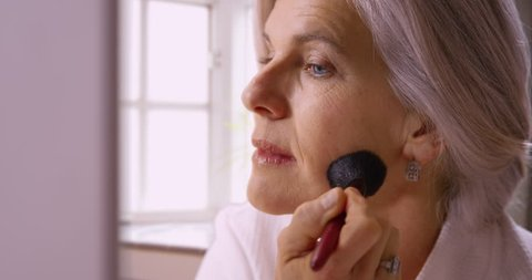 Beautiful mid aged white woman applying makeup. Closeup of lovely elderly woman using makeup to cover natural blemishes.