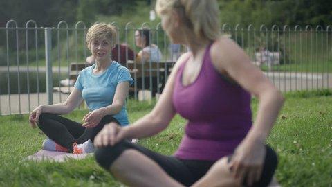 4K Happy mature female friends doing yoga & meditating in the park Dec 2016-UK