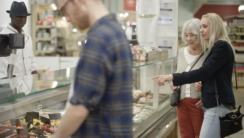 4K Senior lady & adult granddaughter shopping at deli counter in supermarket Dec 2016-UK | Shutterstock HD Video #22857916