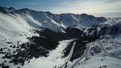 4k Aerial drone footage of highway traffic headed to the ski resort.  Snow covered Colorado Rocky Mountains after a winter blizzard.