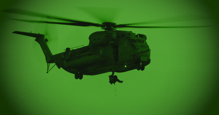 Night Vision footage of Sikorsky CH-53E Super Stallion hovering while a soldier is rescuing a wounded person from combat