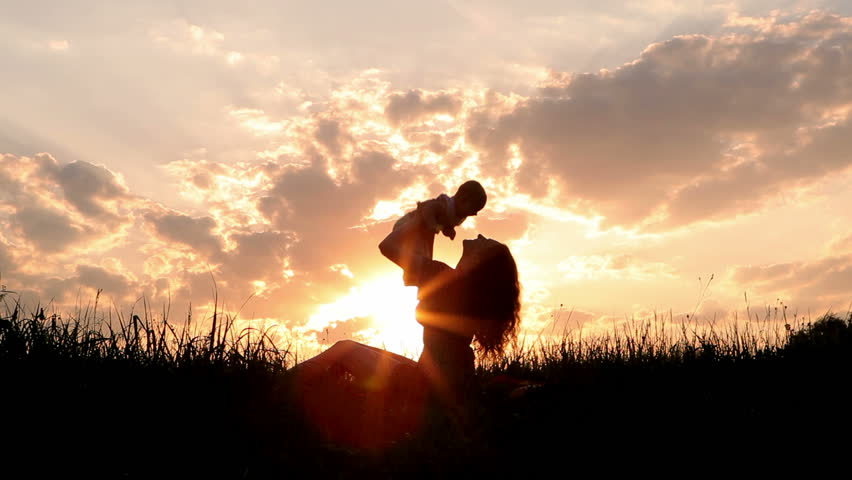Silhouettes happy mother and baby sunset. Mom plays with child and kisses him on the meadow at sunset. Between the glare of the sun