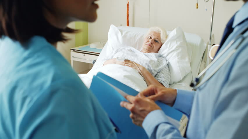 Doctor interacting with each other while patient lying on bed in background 4k | Shutterstock HD Video #22926766