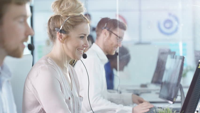 4K Portrait smiling customer service operator taking calls in busy call center Dec 2016-UK | Shutterstock HD Video #22933786