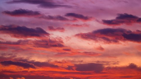 Red, orange, purple, violet, yellow dark sunset sky, clouds timelapse motion video - fast flying, passing, moving, rolling cloudscape, day light to night bright colors dramatic dawn nature background